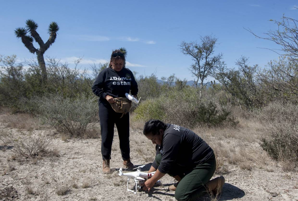 FUNDENL members Hidalgo (left) and Angelica Orozco preparing a drone – to search for missing person remains through ortho photogrametty – to fly over the 'Las Abejas' cooperative land, in the municipality of Salinas Victoria, Nuevo Leon state.