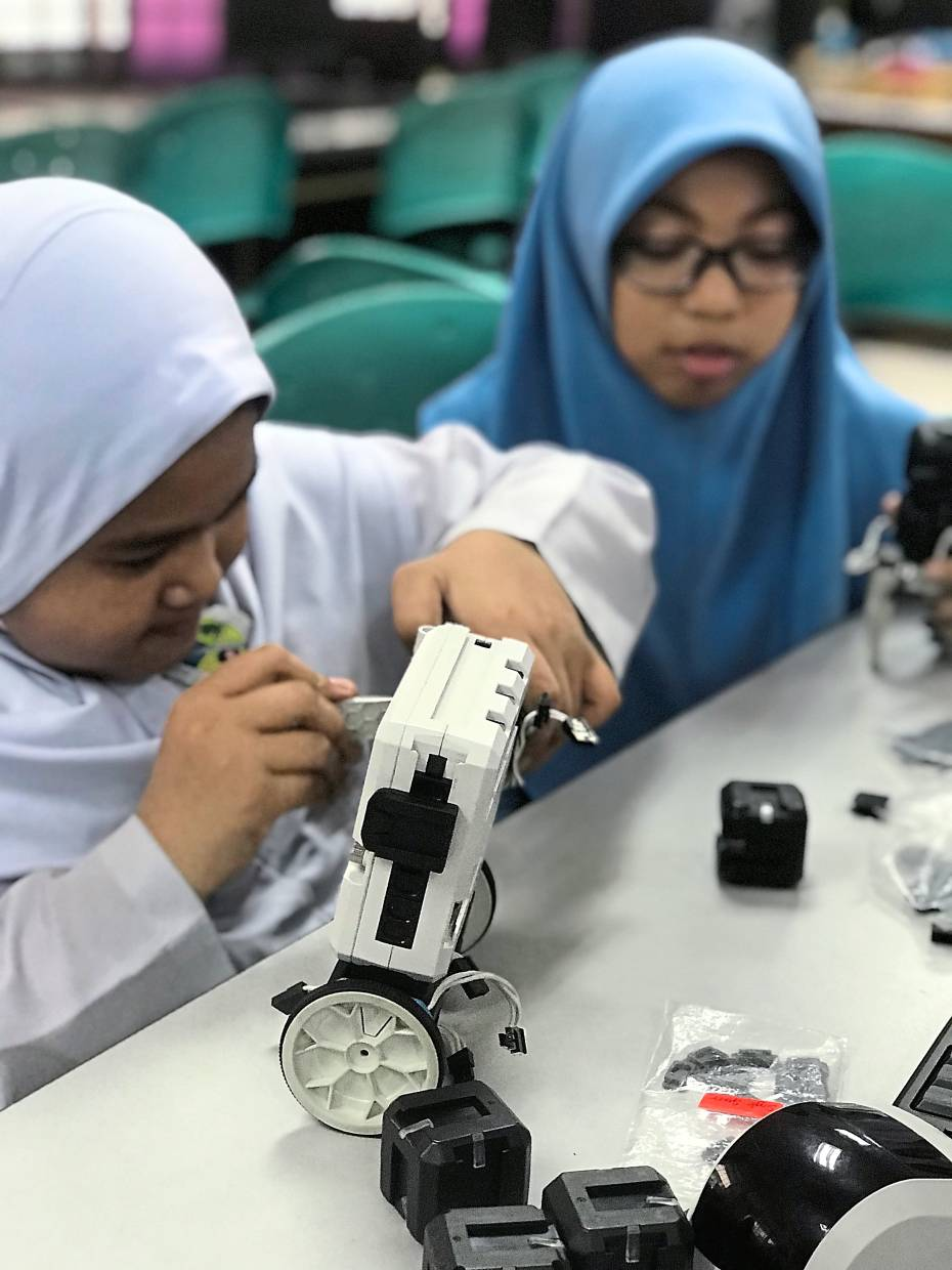 Participants learning to solve issues in their community through robotics. — Arus Academy