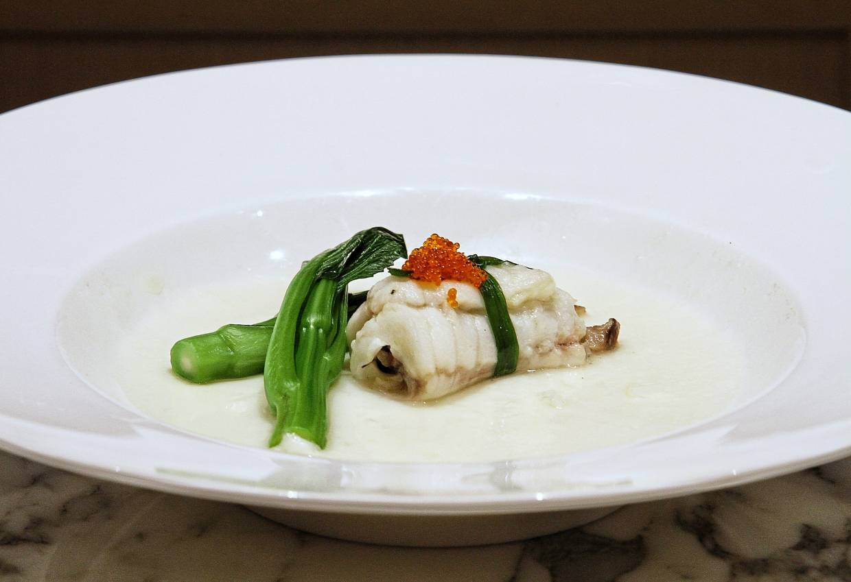 Steamed Dragon Garoupa is a fillet roll on a bed of egg white sauce and topped with red tobiko.