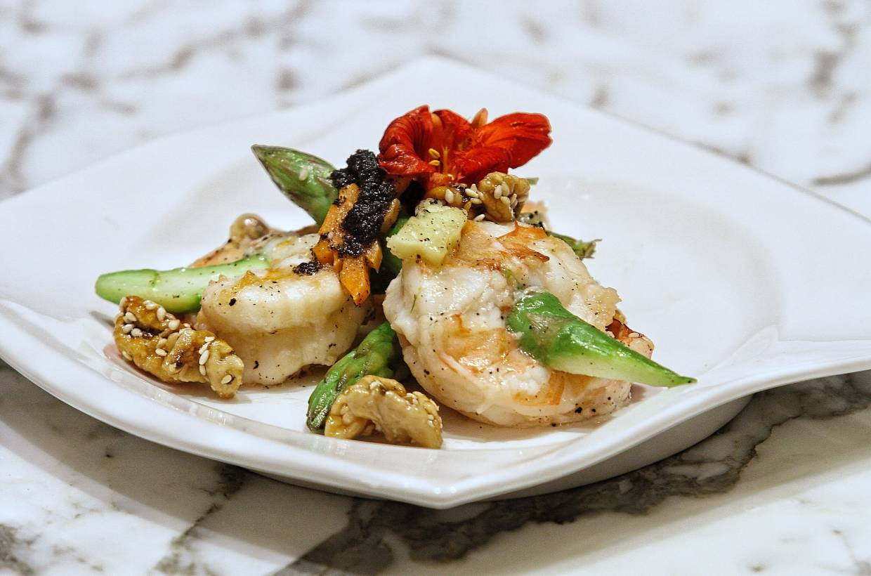 Sautéed prawns stuffed with asparagus, coated with truffle paste and topped with honey walnuts.