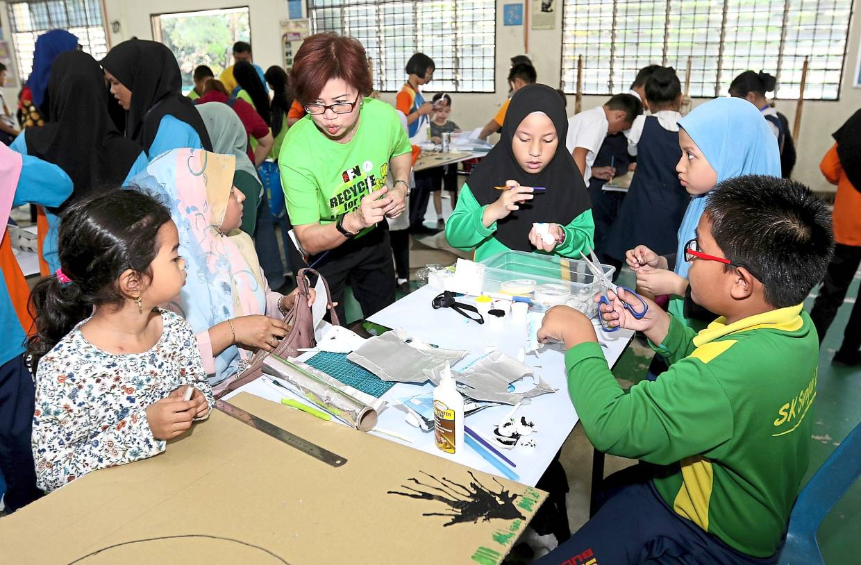 Goh (third left) listening to a comment from a participant of the SK Sungai Dua team    during the poster design competition.