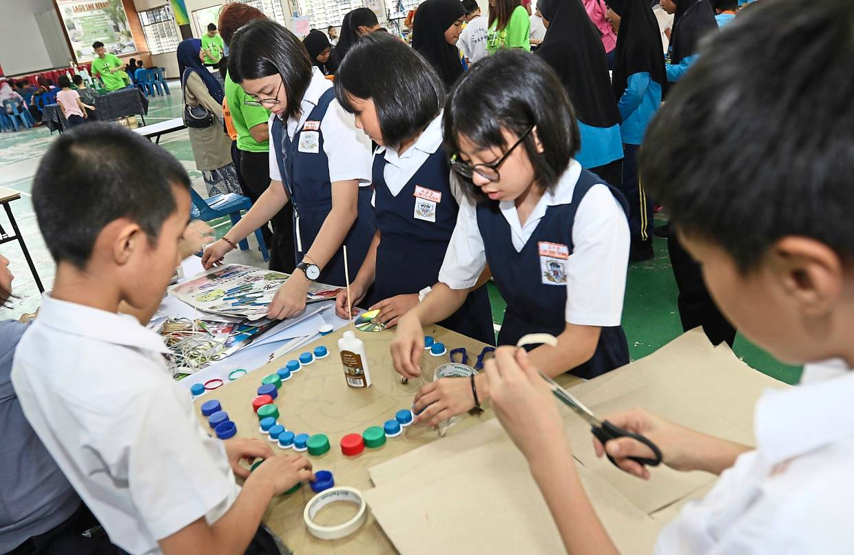 Schoolkids arranging some recyclable items on their competition piece.