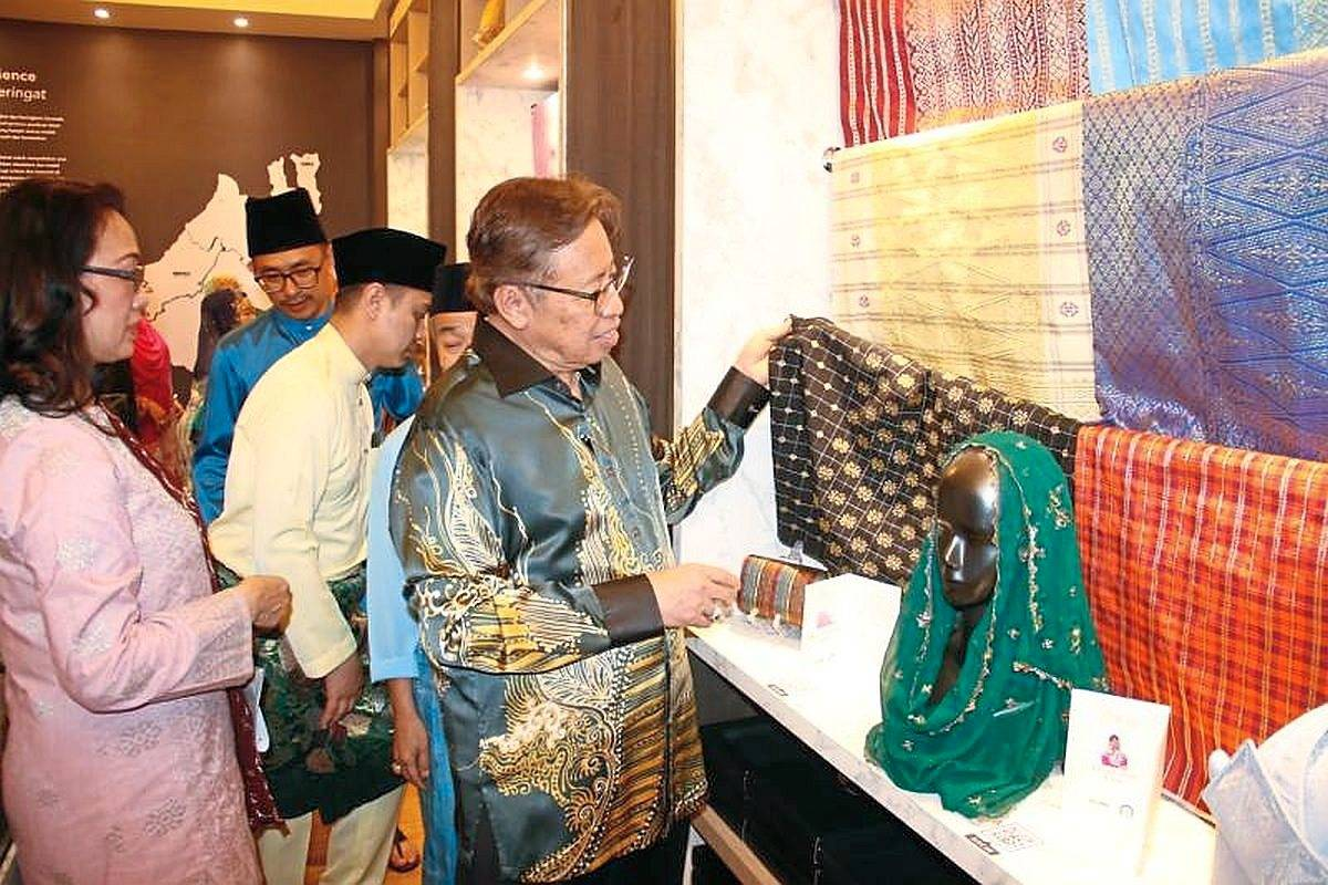Abang Johari (right) taking a closer look at songket showcased at the new gallery. With him is Sabariah (left).
