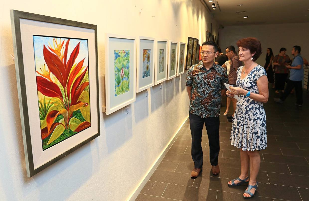 Saint-Arnoult briefing Yeoh on her paintings including 'Garden of Plenty' (left) during the opening of the 'Art Within Theater III: Growth' exhibition at the Performing Arts Centre of Penang. — Photos: ZHAFARAN NASIB/The Star