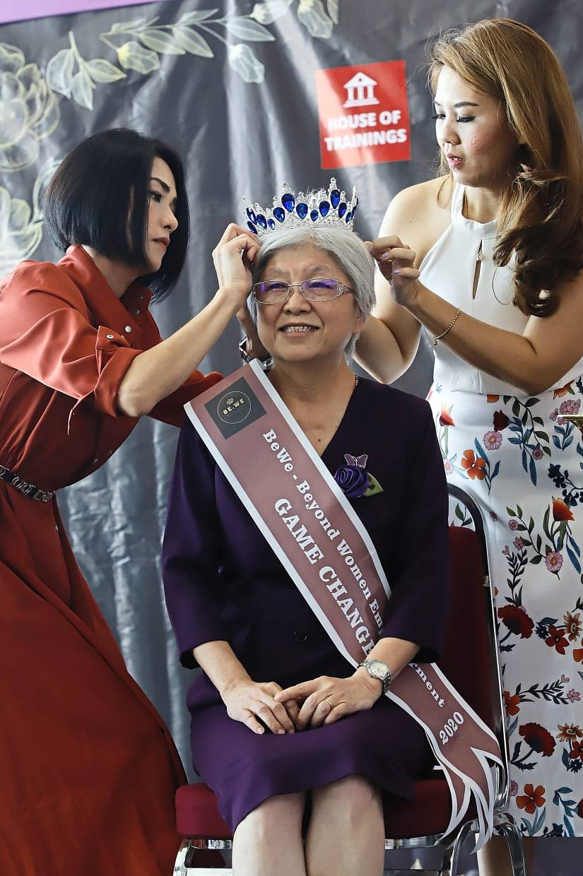 Chong Eng (middle) being crowned as the pageant's Game Changer ambassador for her relentless efforts to look after the welfare of women and the community during the Beyond Women Empowerment Beauty Queen 2020 at 1st Avenue Mall.