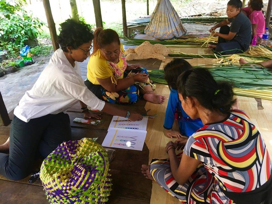 Sasibai (left) meets with the Mah Meri artisans who weave mengkuang for Earth Heir's products. - Earth Heir