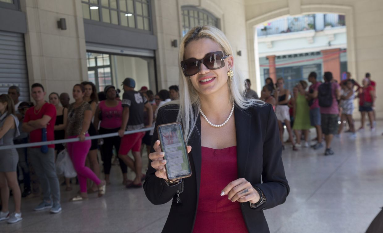 Claudia Santander, a 21-year-old graphic designer, posing with her mobile phone as others line up to buy goods at the 4 Caminos market in Havana, Cuba. Santander administers ten WhatsApp groups that help others search for goods and supplies in Cuba's markets and stores.
