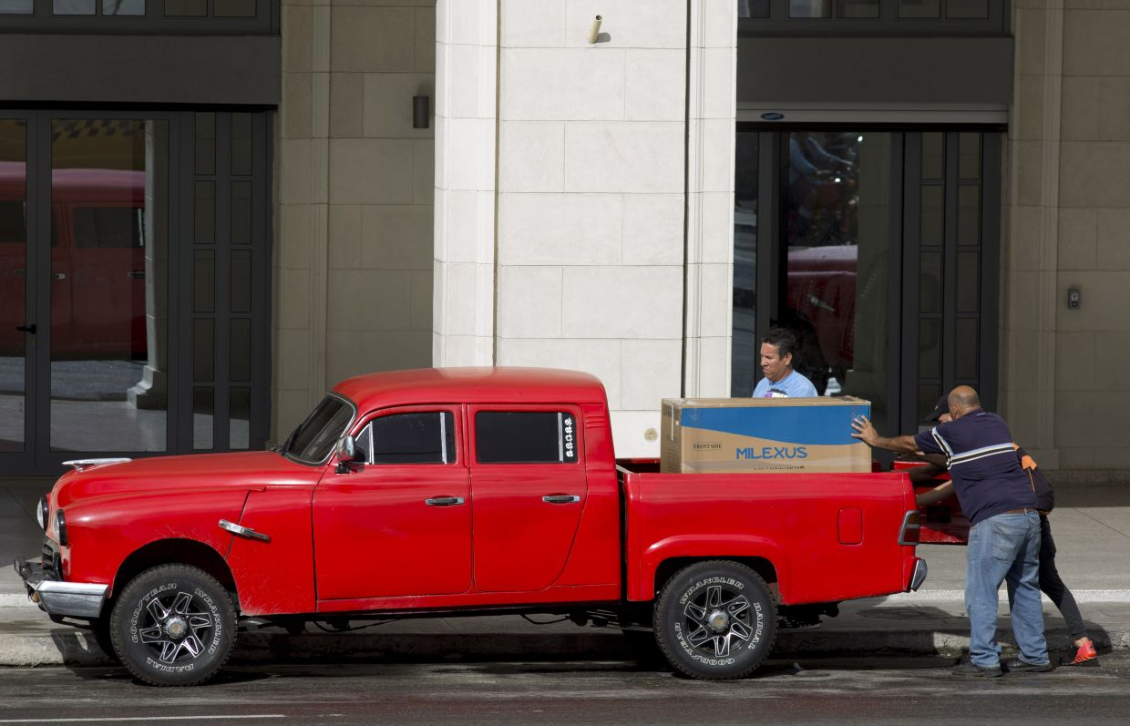 Men loading up a newly bought refrigerator onto a truck in Havana, Cuba. In recent months, Cuban authorities have started to promote websites that allow people to pay in US dollars through a credit card for items including flowers, meat, mattresses and air conditioners. Items like refrigerators are only available to be bought in dollars.