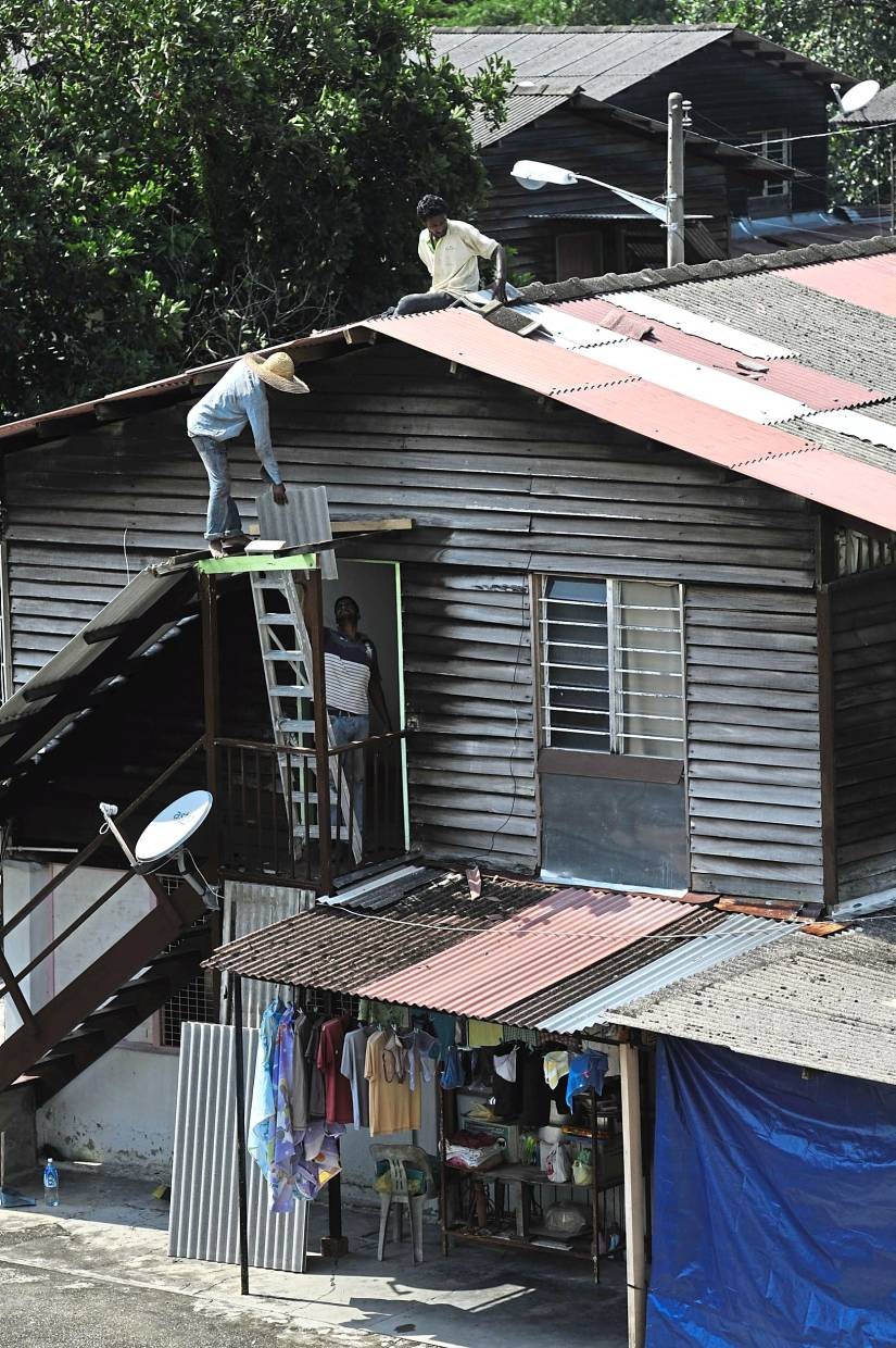 Workers fix the asbestos roof on a house in this filepic. Construction workers are most at risk of developing mesothelioma as they are constantly exposed to asbestos materials.