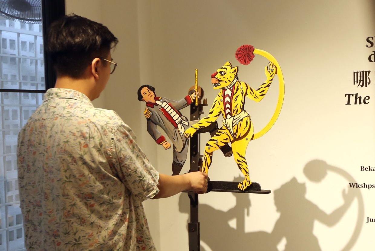 A visitor winds up Captain Thomas Forrest (left) and The Tyger, two hand-cranked whirligigs designed and created by Octo Cornelius and Prihatmoko Moki in collaboration with Soon, on the advice of Rismilliana Wijayanti and Iwan Effendi. Photo: The Star/Izzrafiq Alias