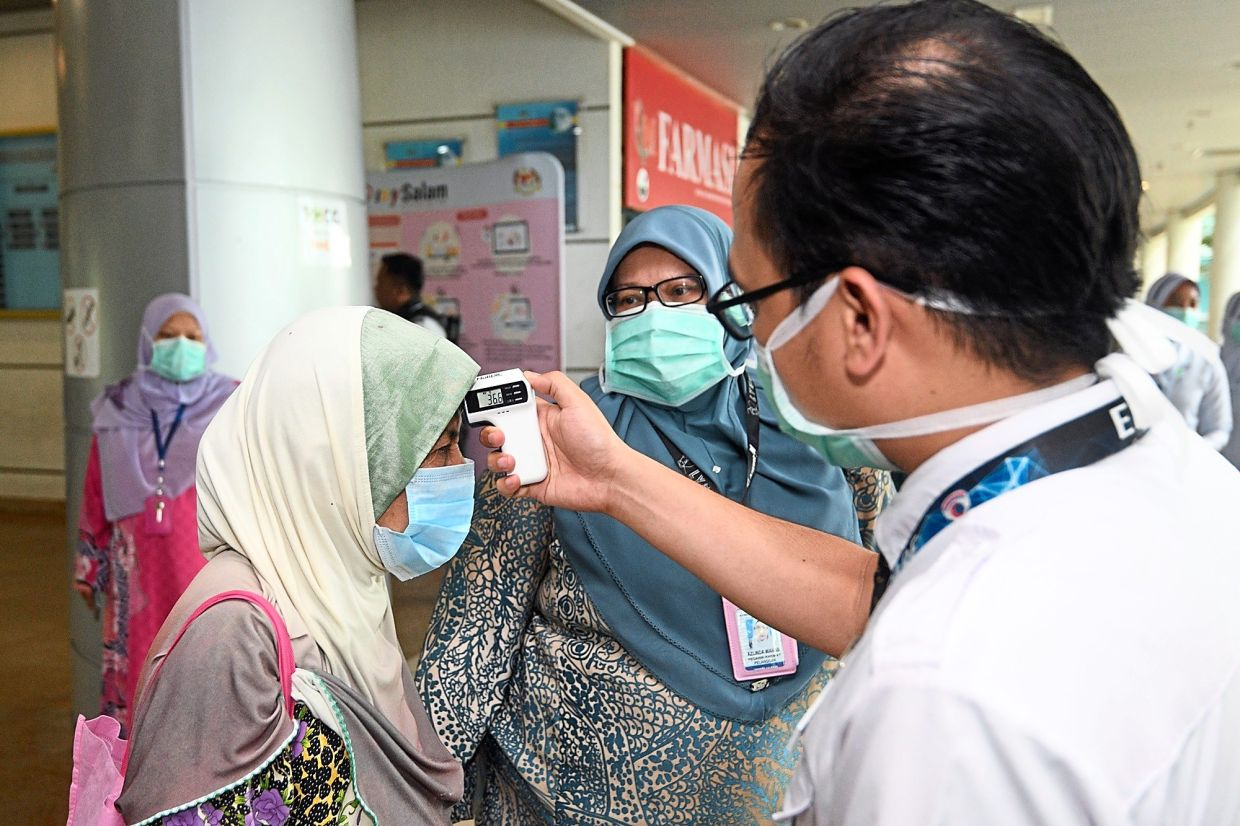 Safety first: Sungai Buloh Hospital staff screening visitors at the entrance. Currently, 26 government hospitals have the capacity to handle the outbreak.