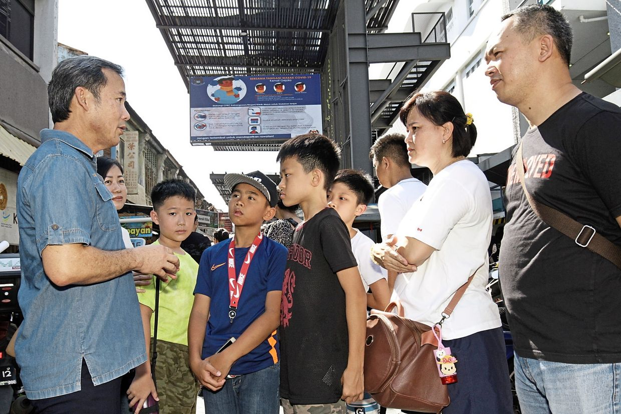 Yew (left) advising several visitors on preventive measures against Covid-19 at the Chowrasta Market.