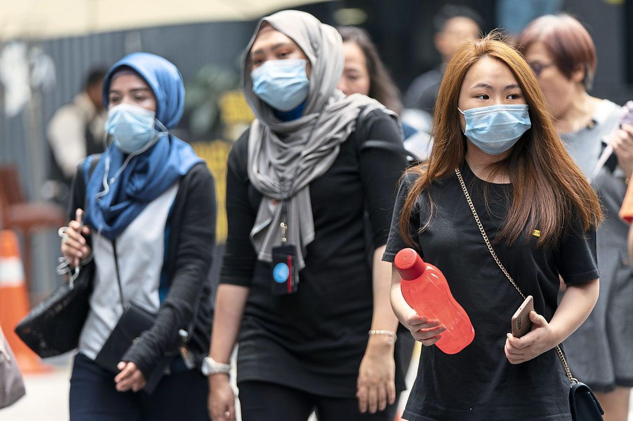 Hospitals get ready: Women wearing protective masks cross a street in Kuala Lumpur. The APHM, which represents all the large private hospitals in Malaysia, is preparing for a possible drastic increase in the number of patients in the weeks ahead. — AP