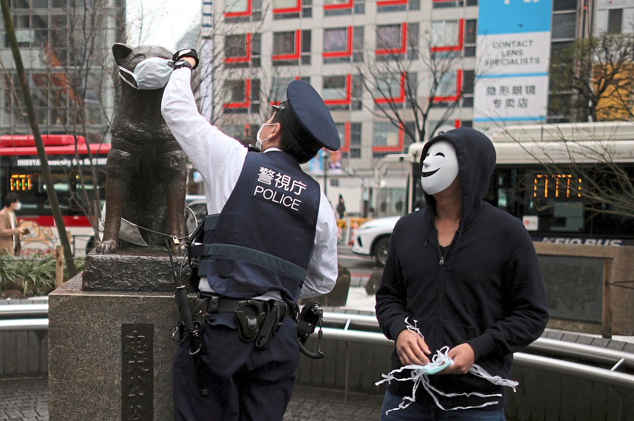 5. It wouldn't be art without mischief. A police officer removes a protective face mask placed over the statue of famous Japanese dog Hachiko, next to a volunteer distributing masks, at Shibuya station in Tokyo. Photo: Reuters