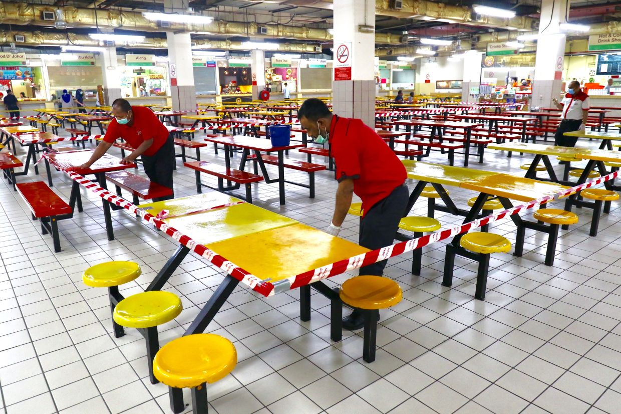 Workers wiping the tables at an empty food court in Mid Valley Megamall. Malaysian government issued a movement order to the public starting from March 18, 2020 until March 31, 2020 to block the spread of COVID-19. FAIHAN GHANI/The Star.