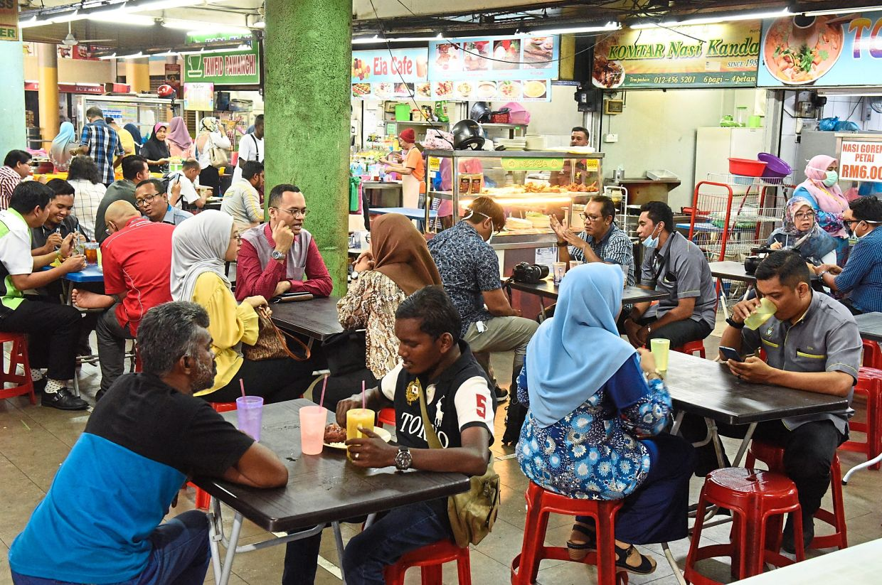 Customers ordering and having their meals as usual at a crowded food court near the Komtar bus interchange on Monday. — Photos: K.T. GOH and MUSTAFA AHMAD/The Star
