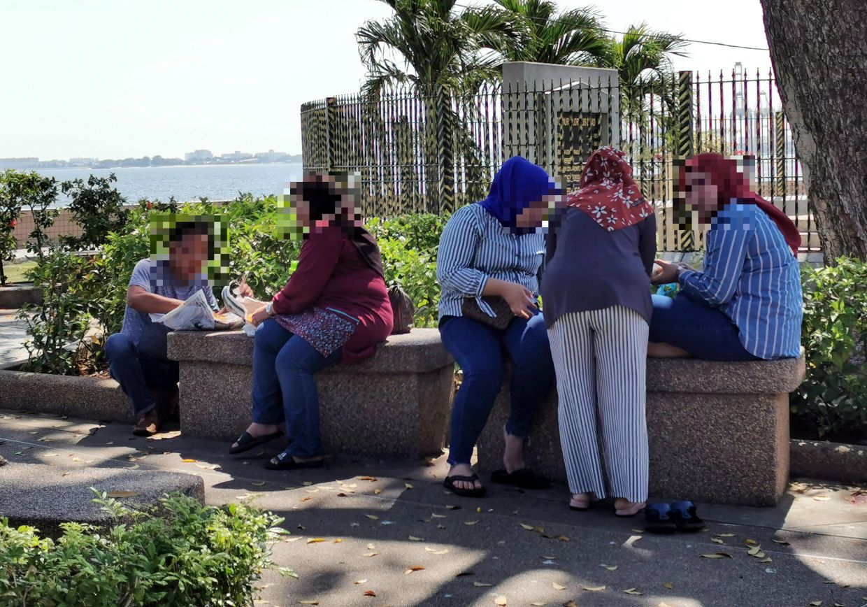 Oblivious to order: People gathering to eat at the promenade area near the Esplanade in George Town.