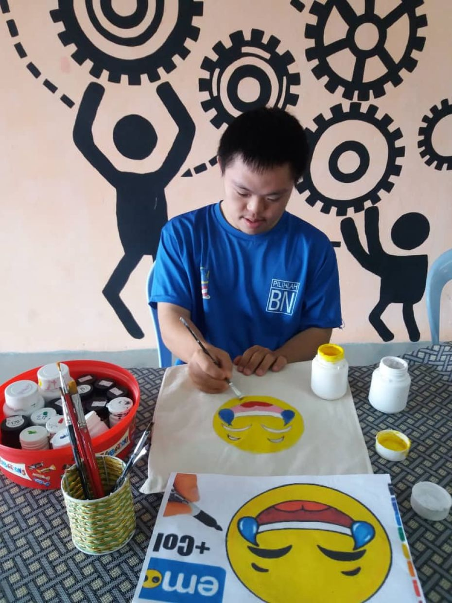 At PAFID's sheltered workshop, a Down Syndrome worker gets to further hone his painting skills and earn a salary. Photo: Perak Association For Intellectually Disabled