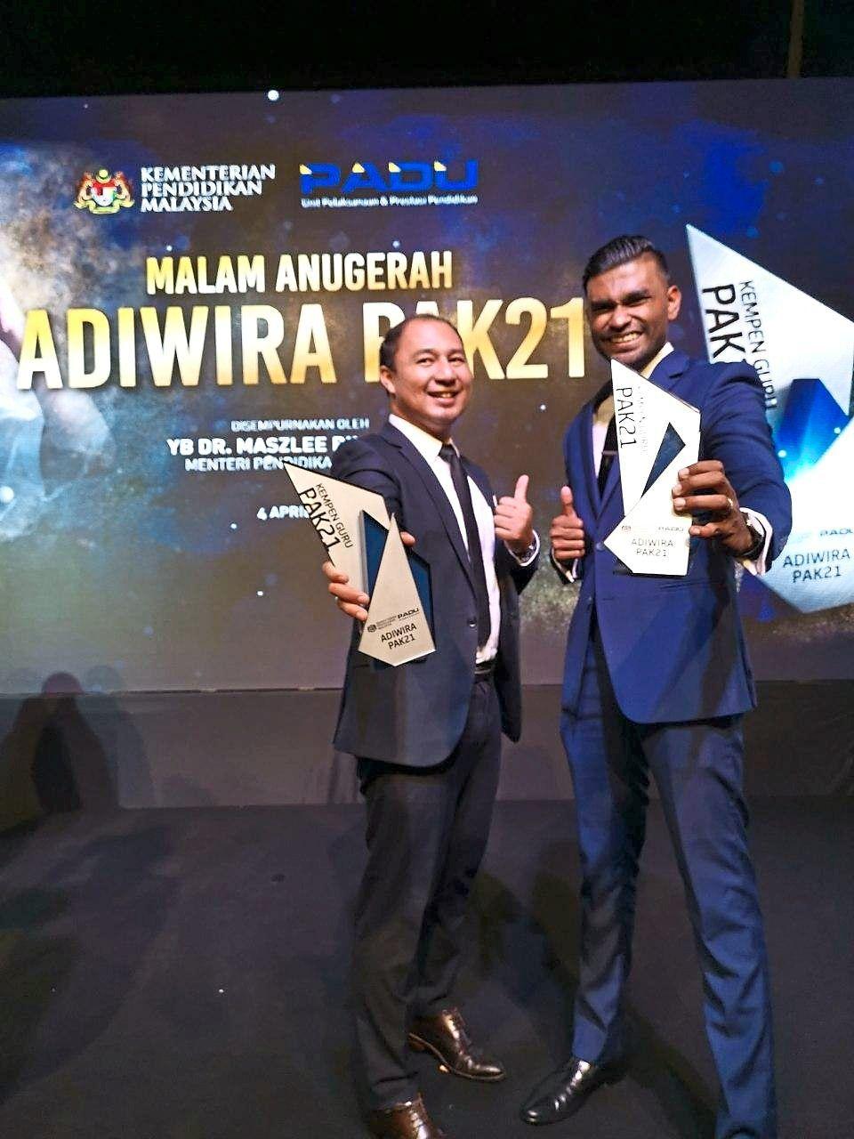 Teaching with pride: Norhailmi (left) and Samuel receiving their Guru Adiwira award last year.