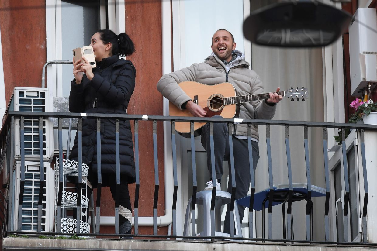 A man singing and playing the guitar from his balcony to raise morale during the lockdown in Italy. You can also sing from your balcony to increase your lung capacity. — Reuters