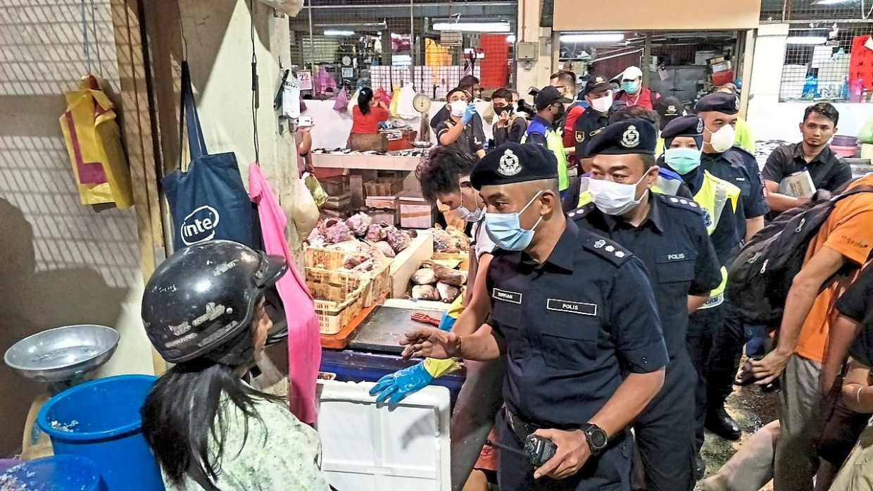 On the beat: George Town OCPD Asst Comm Soffian Santong (front) leading his men and city council enforcement officers at the Ayer Itam market.