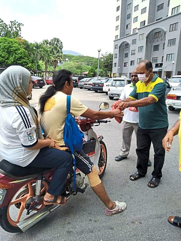 A company representative giving out free food in Alma, Bukit Mertajam.