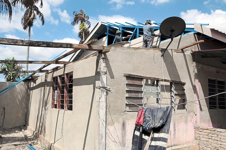 Workers repairing the roofing of Adeeba Raisha's house in Kampung Gerbi, Ayer Hitam in Kubang Pasu.