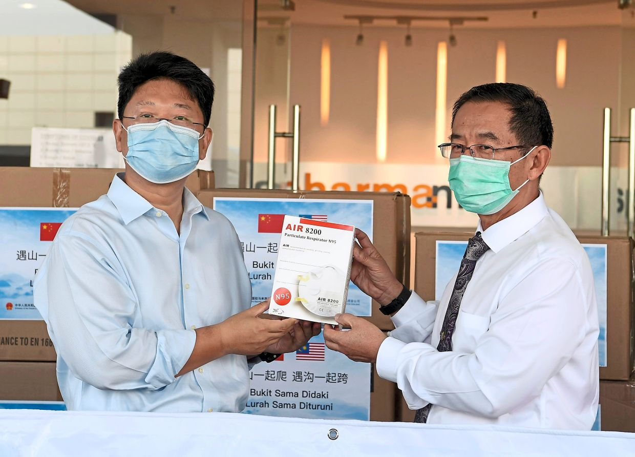 Much-needed help: Health Ministry secretary-general Datuk Seri Dr Chen Chaw Min (right) receiving the donation of medical supplies from Chinese Ambassador to Malaysia Bai Tian at a ceremony in Shah Alam. — Bernama