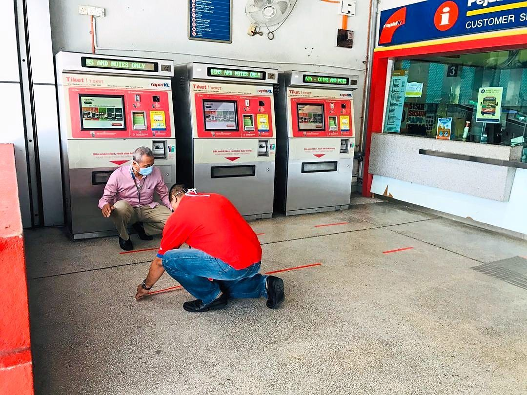 Prasarana employees placing tape on the floor to prevent passengers from standing too close to each other when queueing up to buy tickets at train stations.