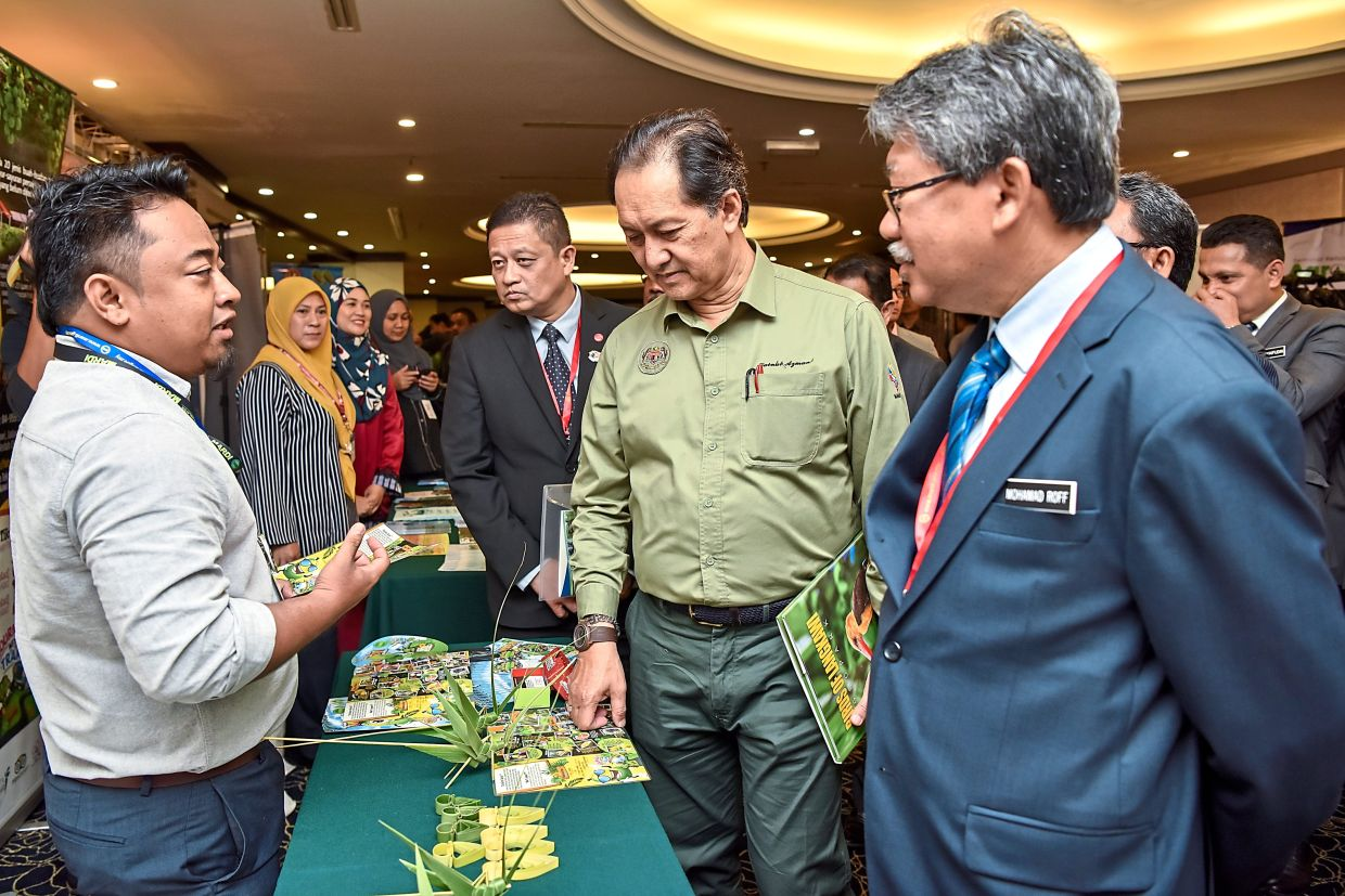 Zainal Azman (in green shirt) and Dr Mohamad Roff (right) chatting with a participant at the seminar.