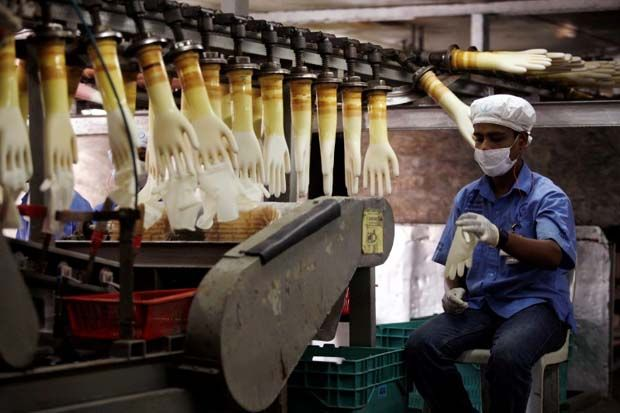 A worker monitors a production line at a Top Glove factory in Meru outside Kuala Lumpur, - Reuters