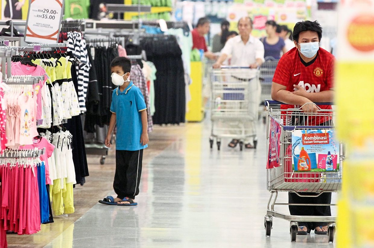 Shoppers wearing facial masks despite being indoor at Tesco Mutiara Damansara.