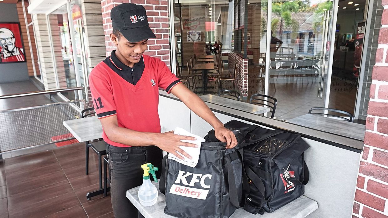 A KFC worker sanitising delivery bags for the next order.