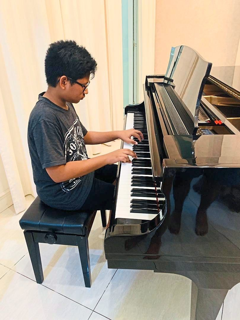 Siblings Zaryl and Lara Ridzuan (below) keep themselves busy during the MCO by playing the piano and painting at home.