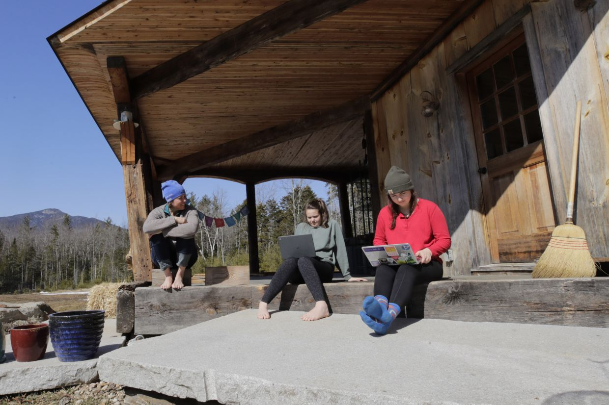 Ashley Bullard, left, sits on the porch of her family's rural home in North Sandwich, New Hampshire, as her daughters Raven, center, a senior in high school, and Willow, right, a freshman at Brandeis University, try to complete their classwork from home during the virus outbreak on a very limited Internet connection. — AP