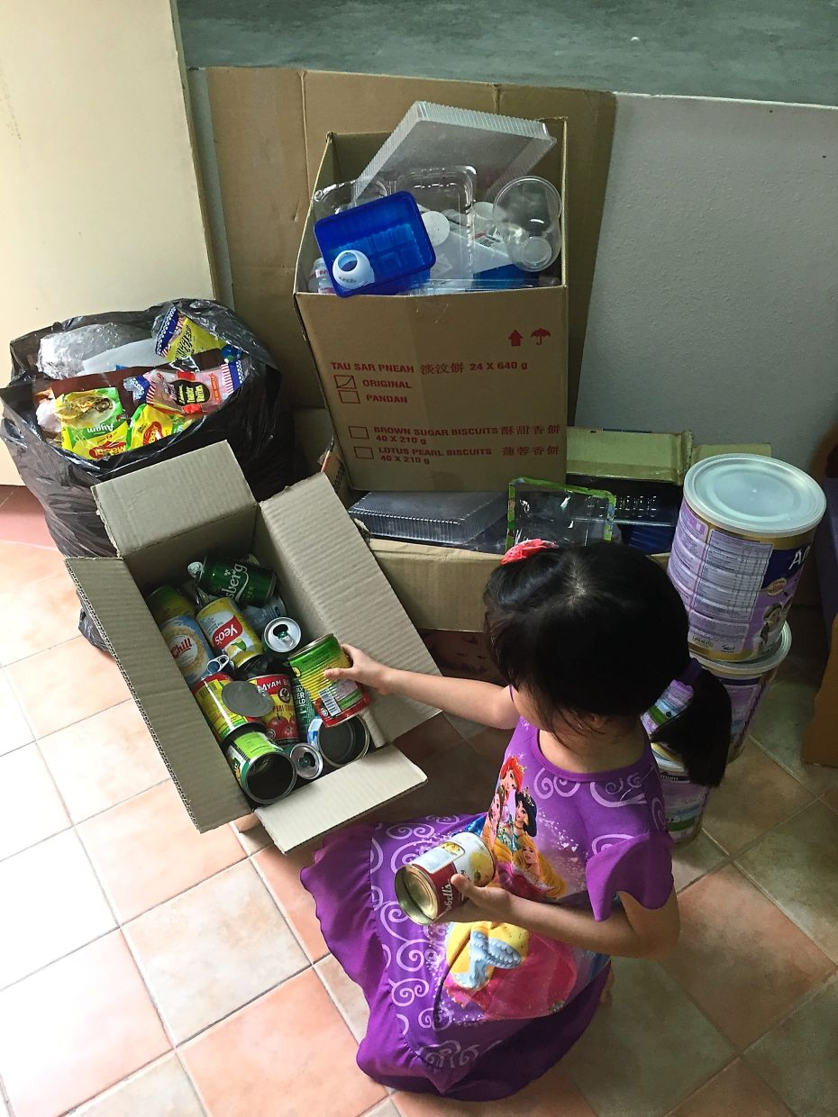 A child putting empty cans away for recycling at her home in Penang.