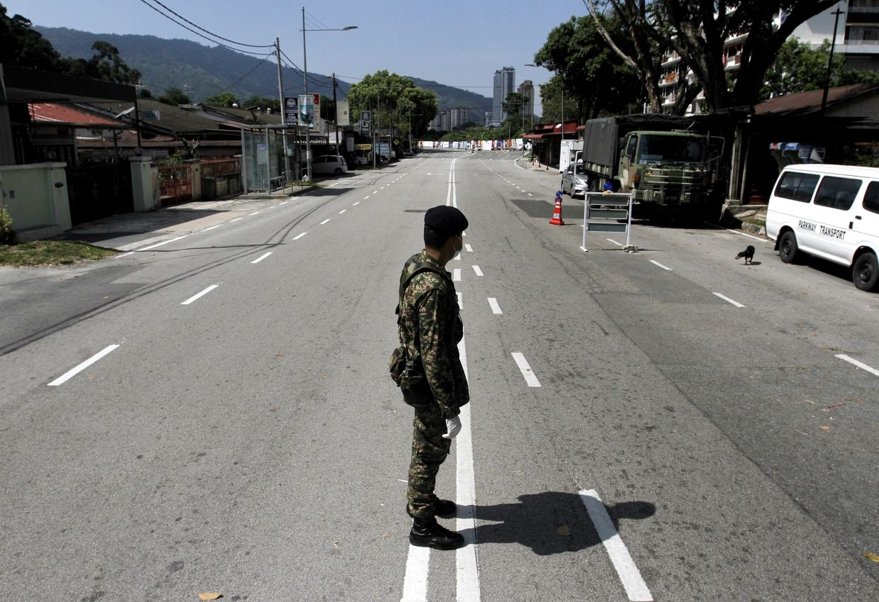 Authorities manning a road block at a near-empty street. Penang police have announced a 97.8% compliance rate. — Filepic
