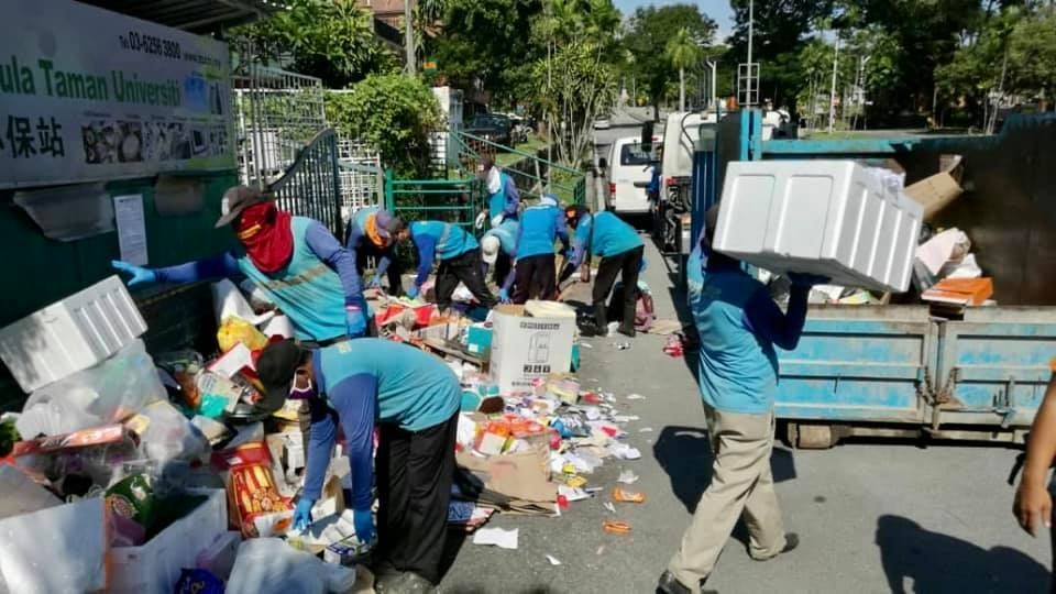 KDEB workers clearing the mountain of rubbish left at the front gate of Tzu Chi recycling centre in Taman Universiti Indah, Seri Kembangan.