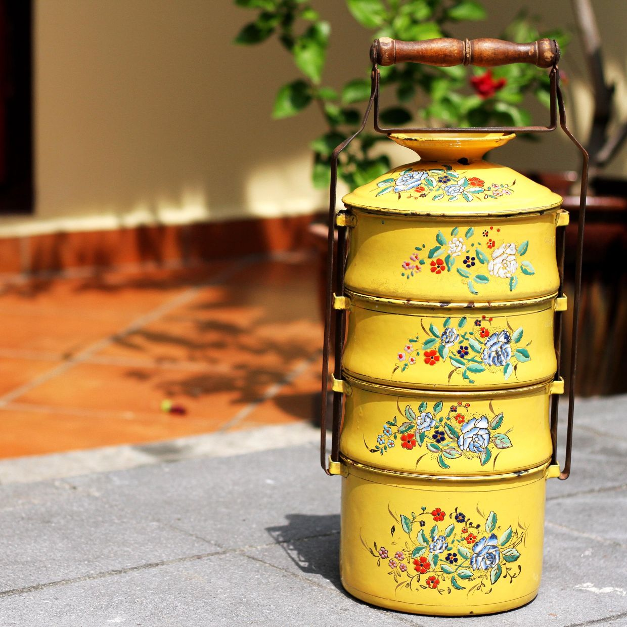 A 1920s tiffin manufactured by Katz Brothers made from enamel with a wooden handle and an iron locking mechanism. Both sides of this tiffin are adorned with hand-drawn floral designs. Due to its colour and design, it is one of the rarest pieces available in the market. Photo: Umachandran Ramiah