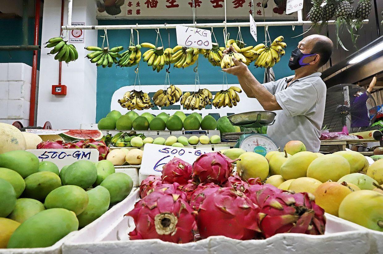 A trader arranging fruits at his stall during the MCO at the Batu Lanchang market in Penang.