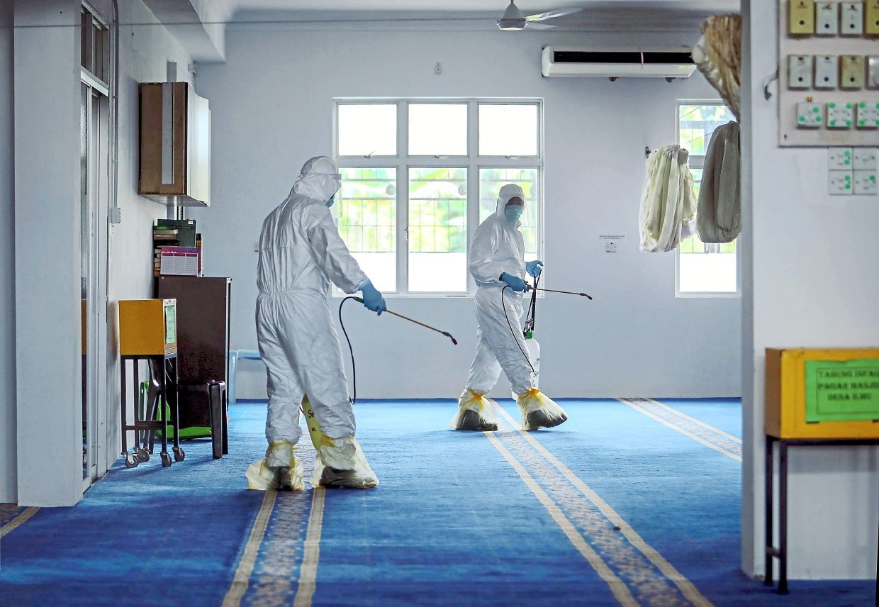 Fire and Rescue personnel disinfecting a mosque in Kota Samarahan to curb the spread of Covid-19. - Filepic
