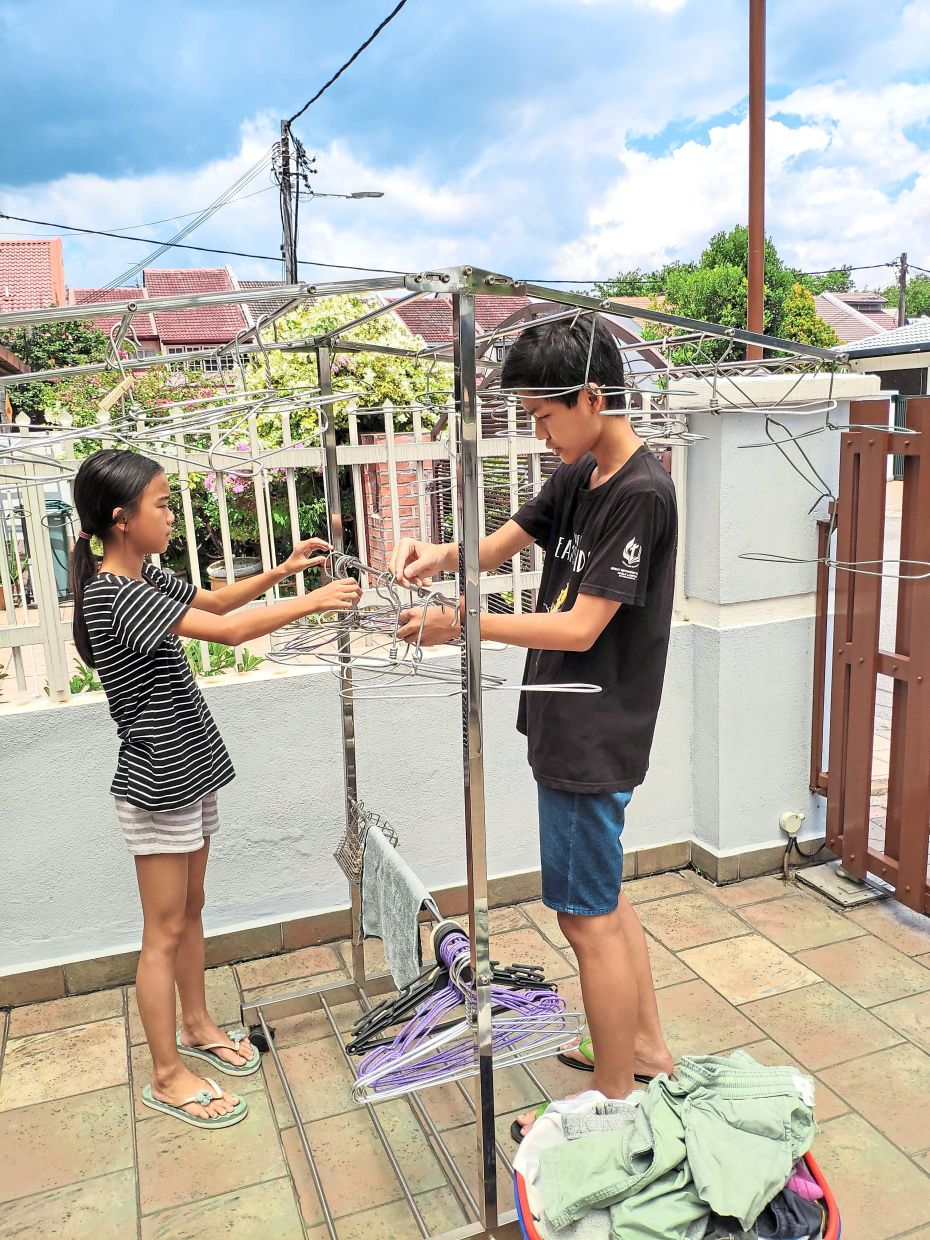 Jayden (right) and his sister Jenelle helping with the laundry.