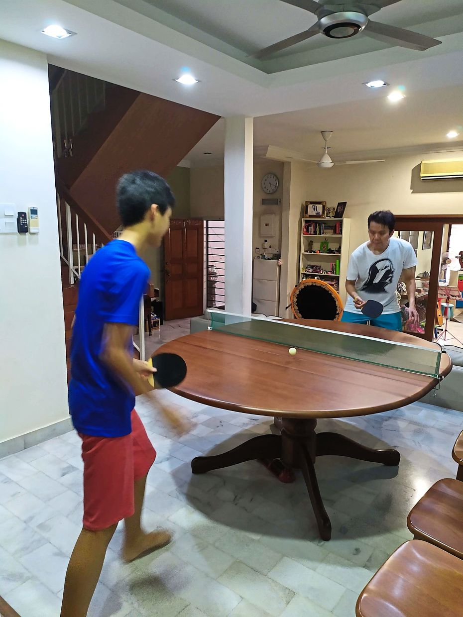The Ho family's dining table is now a ping pong table for recreation.