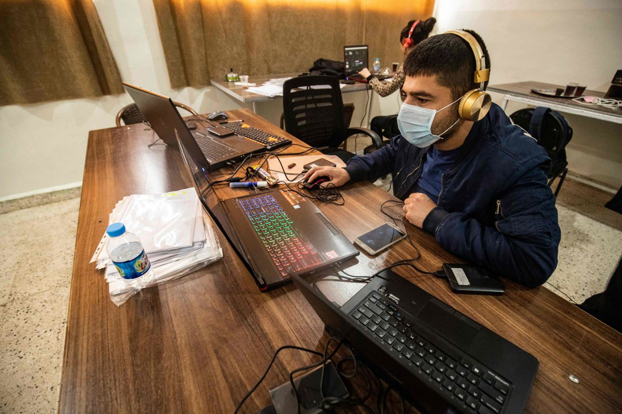 Technicians from the Kurdish educational authorities, edit and prepare recorded classes to be broadcast on local television and Youtube for distance learning, in the Kurdish-majority city of Qamishli in Syria's northeastern Hasakeh province, amid the novel coronavirus pandemic, on April 4, 2020.