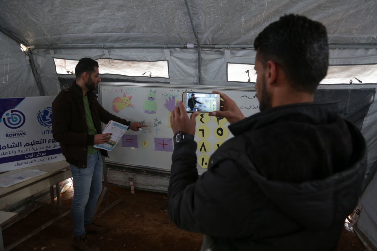 A man films a mathematics lesson by teacher Ahmed Rateb in a makeshift classroom inside a tent, in a camp for displaced Syrians in the village of Kafr Yahmoul in the northwestern Idlib province, to be broadcast for distance learning, amid the coronavirus pandemic on April 3, 2020.