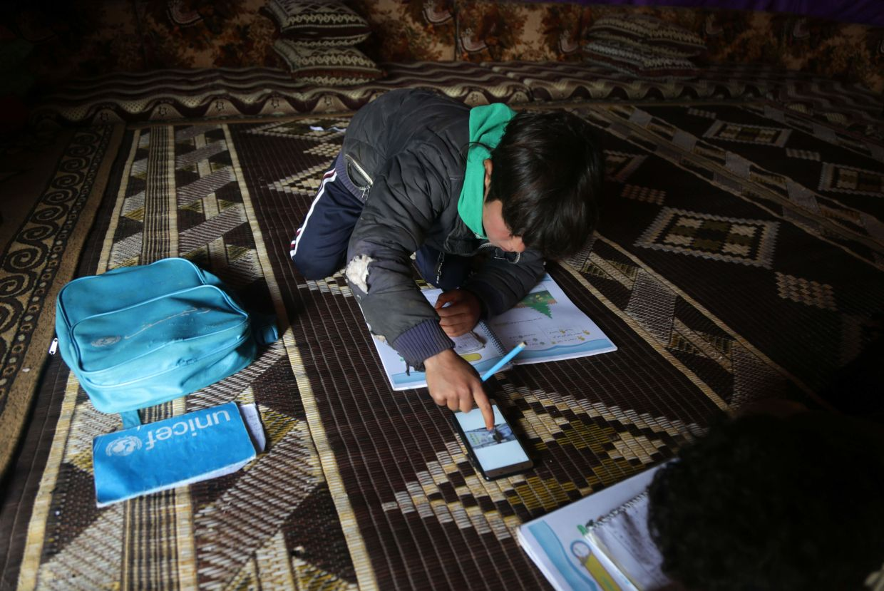 A young pupil follows a lesson on a mobile telephone inside a tent, in a camp for displaced Syrians in the village of Kafr Yahmoul in the northwestern Idlib province, amid the coronavirus pandemic on April 3, 2020.