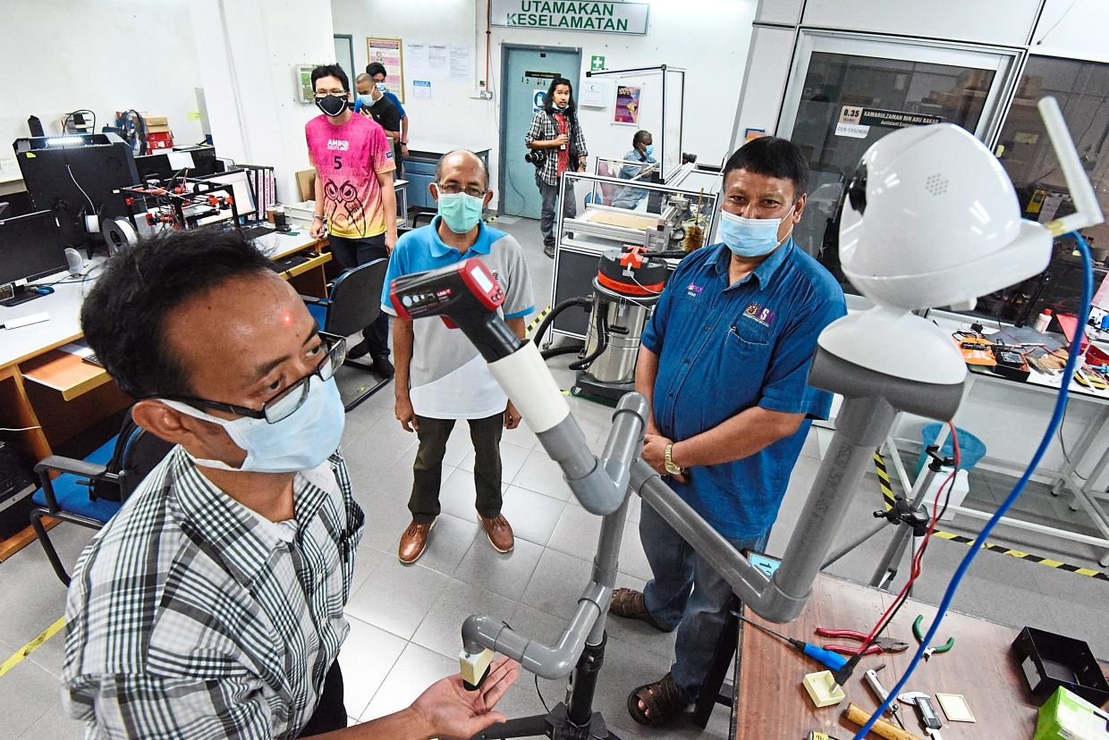 (From right) prof Nor Azazi and Prof Mohd Fadzil observing a staff member using the non-contact temperature reader before entering the tunnel.