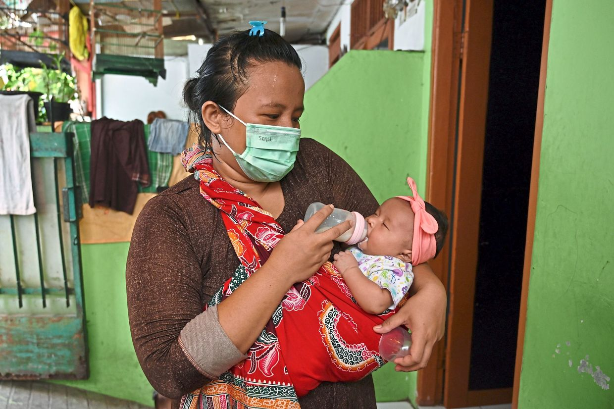 A (healthy) mother feeds her one-month-old baby while wearing a face mask at home in Tangerang, Indonesia. Mothers with Covid-19 should practice hand hygiene and wear a face mask before interacting with their babies. — AFP