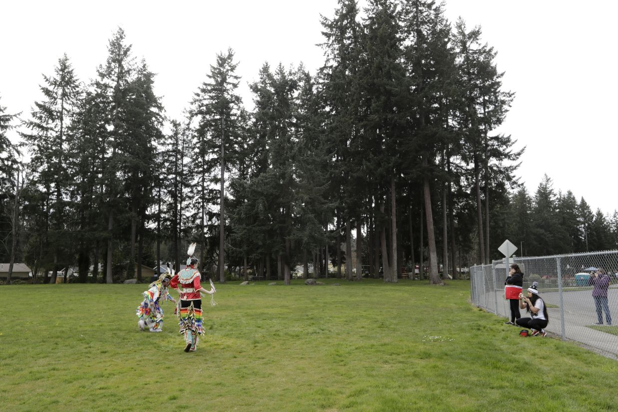 Wakiyan Cuny, left, and his sister Wicahpi Cuny, Dakota and Lakota tribal members, are filmed by their mother Tera Baker during a live streamed powwow from a park near their home, in Puyallup, Washington.