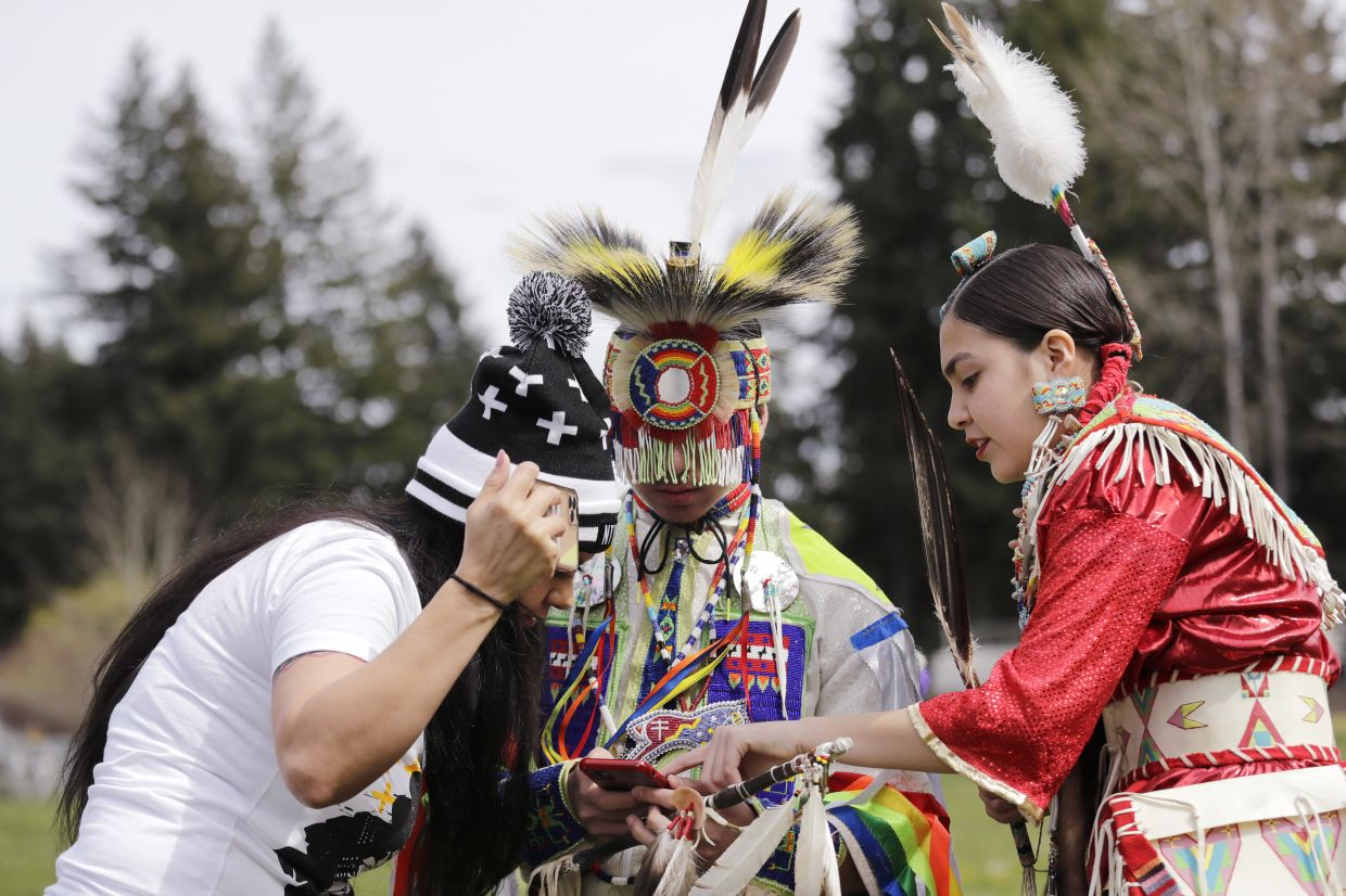 Tera Baker, left, huddles over a cellphone with her children Wakiyan Cuny, center, and Wicahpi Cuny, all Dakota and Lakota tribal members, during a live streamed powwow from a park near their home in Puyallup, Washington.